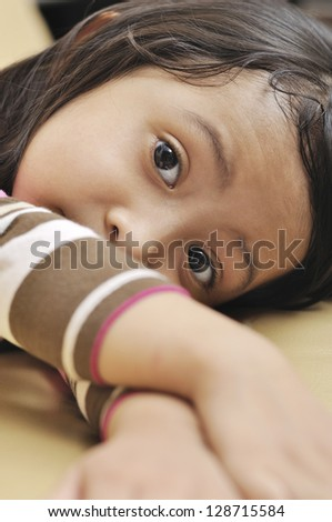 Beautiful young girl look emptily looking at the camera on the couch