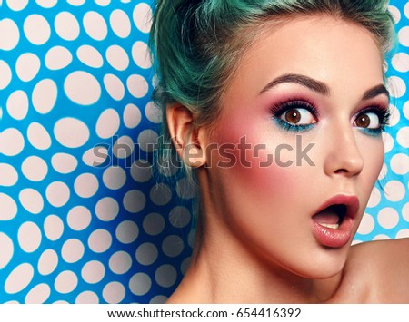 Beautiful young girl looks surprised. A large portrait is a face. Blue hair. Blue bright background in white peas. On the face of emotion - joy, surprise, surprise. Celebration and fun. #654416392