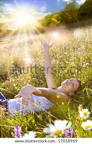 beautiful young girl lying in a sunset marguerite meadow