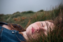 Beautiful young girl, lying in the grass. Eyes closed.