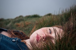 Beautiful young girl, lying in the grass. Eyes opened.