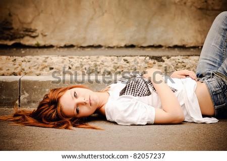Beautiful young girl lying on the street
