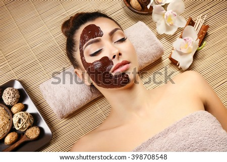 Beautiful young girl lying with chocolate mask in spa salon