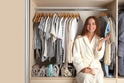 Beautiful young girl next to the wardrobe. Stylish wardrobe. Clothing storage concept.