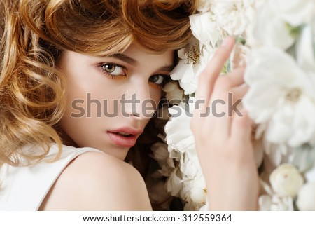 Beautiful young girl on a background of white flowers, the concept of beauty and health