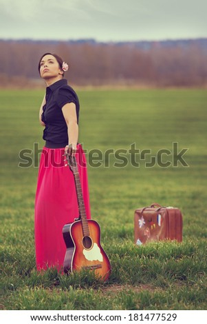 Beautiful, young girl on a meadow taking a break from a long journey