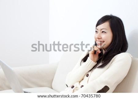 beautiful young girl on a sofa with notebook computer