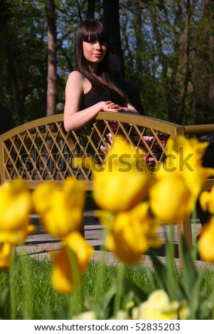 beautiful young girl on the green grass with red tulips - stock photo