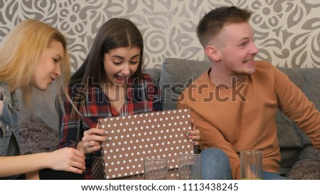 Stock Photo Beautiful young girl opens a gift box and is surprised and happy with what she sees
