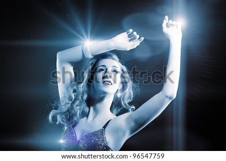 Beautiful young girl or woman dancing in a club disco to the music, lots of lights visible