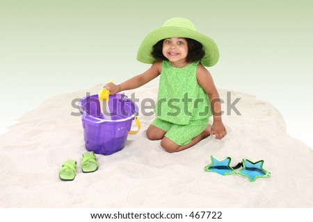 Beautiful Young Girl Playing In the Sand in green summer clothes and big green hat.  Beautiful eyes.