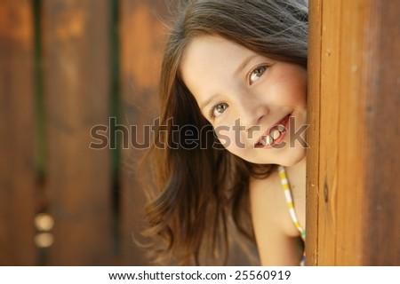 beautiful young girl portrait playing hidden behind the wooden door