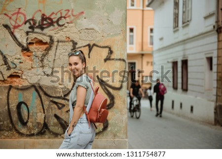 Beautiful young girl posing in old town with graffiti, in jeans fashion with backpack and sunglasses