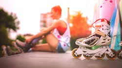 Beautiful young girl puts on roller skates in skate park. Sunset light. Colorized
