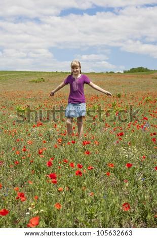 Beautiful young girl running across a poppy field.