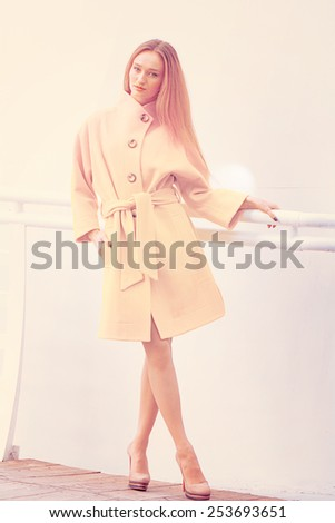 Beautiful young girl showing fashionable yellow coat on a light background wall