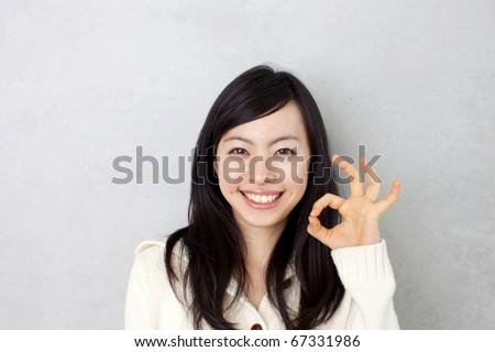 beautiful young girl showing OK sign