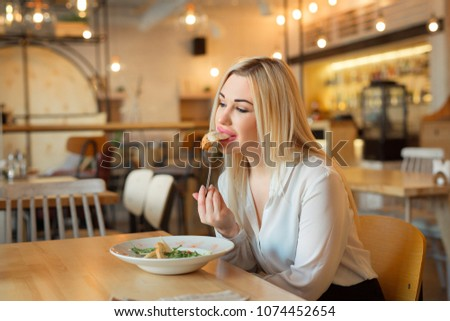 beautiful young girl sitting in a restaurant eating a salad #1074452654