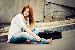 Beautiful young girl sitting on asphalt