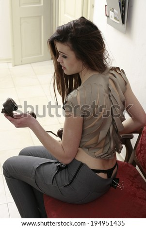 beautiful young girl sitting on the sofa holding an old telephone, stylish furniture in the old apartment