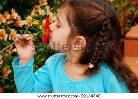 beautiful young girl smelling a red flower