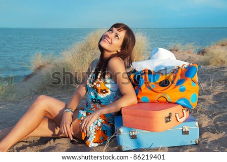 Beautiful young girl smiling and looking up. She dreams of a happy journey. She sits on the sand against the sea and next to her suitcases.