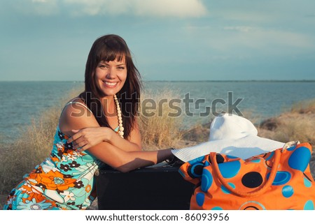 Beautiful young girl smiling. She sits on the background of the sea with their bags.