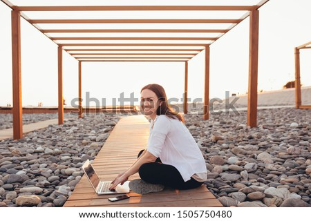 Beautiful young girl student resting sitting on a wooden platform among the stony beach on a sunny summer day. Concept of rest from study