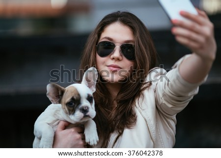 Beautiful young girl taking a selfie with her French bulldog puppy. Focus is on girl. #376042378
