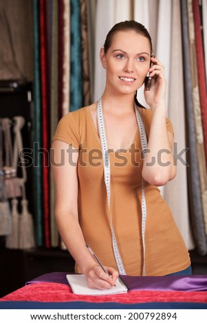 beautiful young girl talking on phone. waist up brunette standing in store and writing
