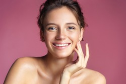 Beautiful young girl touching her perfect skin on pink background. Skin care concept