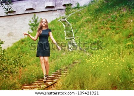Beautiful young girl walks through the park