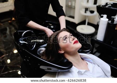 Beautiful young girl washing her head in a beauty salon #626626838