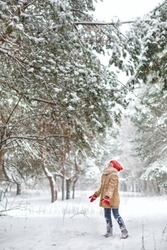 Beautiful young girl wearing a beige down jacket and red knitted hat and scarf playing in a snowy winter park on Christmas day. Child playing with snow in winter. Kid play and jump in snowy forest
