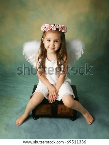 Beautiful young girl wearing angel wings and flower halo with smile happy expression