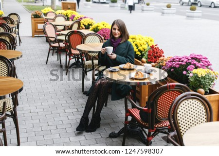 Beautiful young girl wearing green coat sitting at a table in cozy street outdoor cafe and drinking coffee with a croissant. Restaurant terrace is decorated with chrysanthemum flowers bushes in autumn