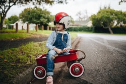 Beautiful young girl wearing helmet sitting in a red wagon cart by the road outdoors. Cute little girl in a toy trolley outdoors.