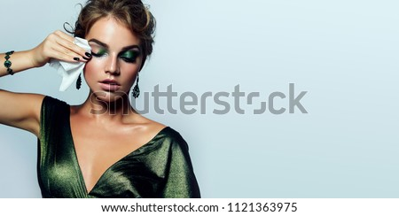 beautiful young girl with a bright make-up and in a shiny green dress striatet makeup from her face with a wet napkin. Hairstyle - curls are gathered in a bun.