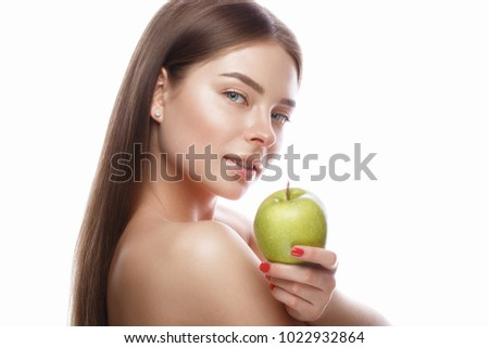 Beautiful young girl with a light natural make-up and perfect skin with apple in her hand. Beauty face. Picture taken in the studio on a white background.