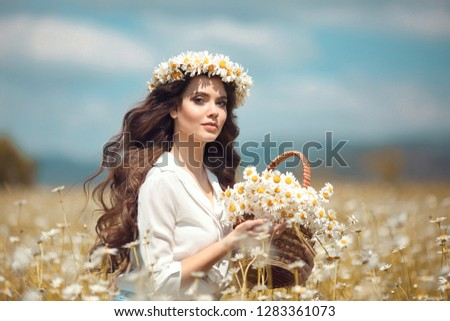 Beautiful young girl with basket of flowers over chamomile field. Carefree happy brunette woman with healthy wavy hair having fun outdoor in nature.  #1283361073
