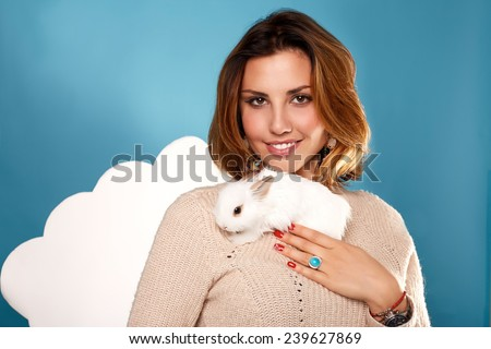 Beautiful young girl with blond hair bright with natural make-up smiling red manicure wearing beige warm sweater is holding the white fluffy little rabbits on a background of blue sky and white clouds
