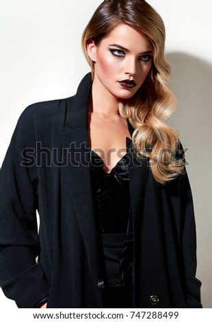Beautiful young girl with blond hair in fashionable black clothes - a long jacket and boots.Makeup, cosmetics, make-up artist,beauty salon, hair,hairstyle, Hollywood chic, styling,stylist,hairdresser.