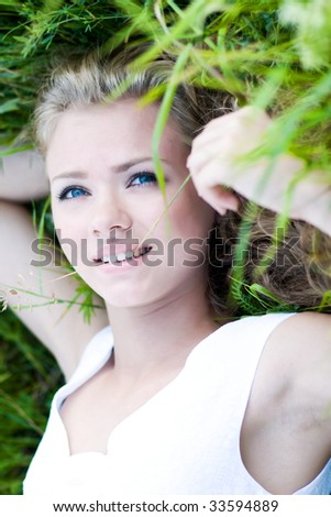 Beautiful young girl with blue eyes lie on green grass