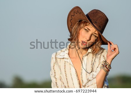 Beautiful young girl with brown golden curls hair in a cowboy hat sexy looking and posing on the blue sky background on the fashion model photo shooting. Summer heat outside, environment