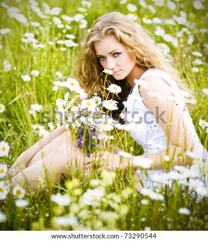 Beautiful young girl with curly white hair in camomile field