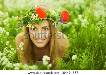 Beautiful young girl with diadem on green field