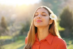 Beautiful young girl with flower on ear enjoying, relaxing, feeling alive, breathing fresh air, got freedom from work or relations, calm and dreaming with closed eyes in green park
