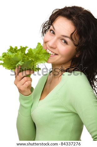 Beautiful young girl with green lettuce leaf, isolated over white - stock photo