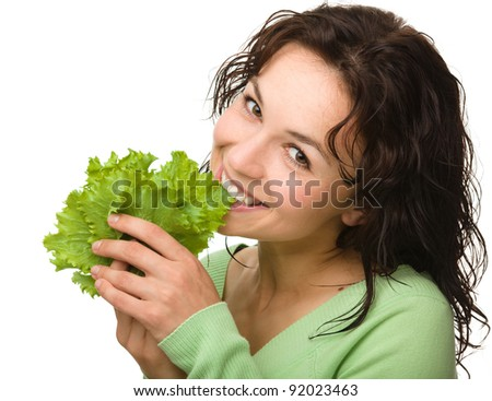 Beautiful young girl with green lettuce leaf, isolated over white