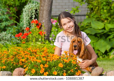 Beautiful young girl with her dog near flowers, English Cocker Spaniel - stock photo